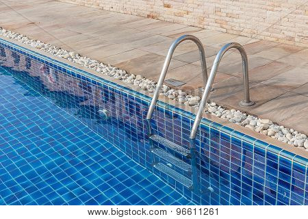 The Metallic Ladder With Clear Blue Swimming Pool.