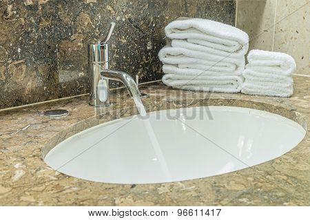 Washbasin And White Towel In Bathroom