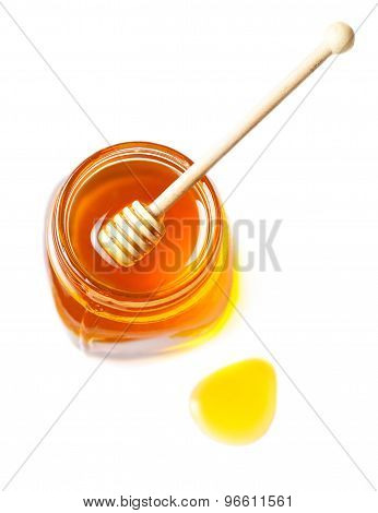Honey In A Glass Jar With Honey Dipper Isolated On White Background Close Up. Fresh Honey With A Sti