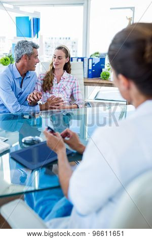 Pregnant woman and her husband discussing with doctor in clinic