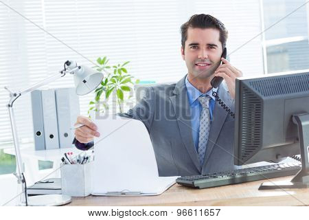 Portrait of a professional businessman checking at his notebook while on the phone