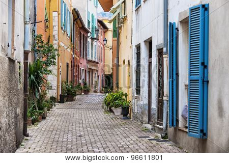 Cobblestone street with colourful buildings and potted plants in old medieval town Villefranche-sur-Mer on French Riviera, France.