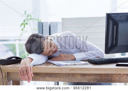 Tired businesswoman sleeping at her desk in her office