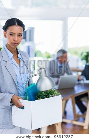Businesswoman holding box and looking at camera at office