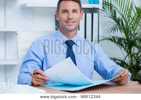 Smiling businessman reading a contrat beore signing it in the office