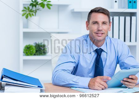 Portrait of smiling businessman using her digital tablet in the office