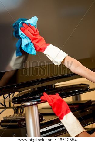 Closeup Of Woman In Rubber Gloves Cleaning Tv Screen With Rag