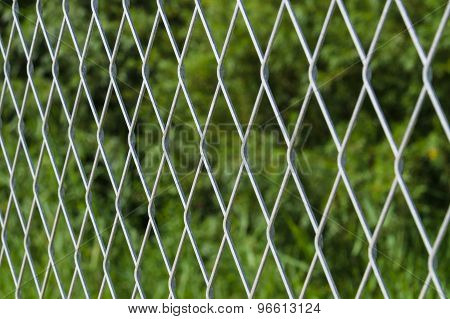 Blurred Metallic Mesh Fence Against Green Background