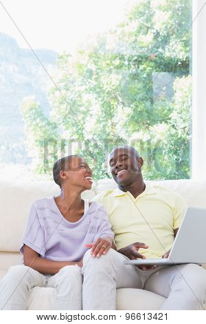 Happy smiling couple using laptop on couch in living room