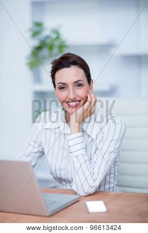 Pretty brunette smiling businesswoman using laptop at the office