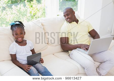 Happy smiling father using laptop and her daughter using tablet on couch in living room