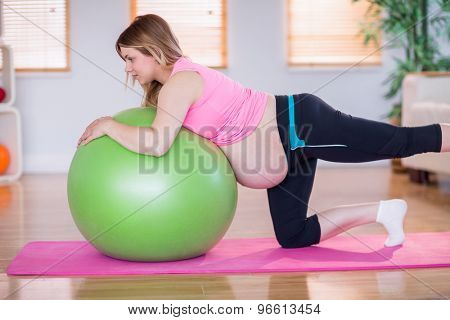 Pregnant woman doing exercise with exercise ball at home