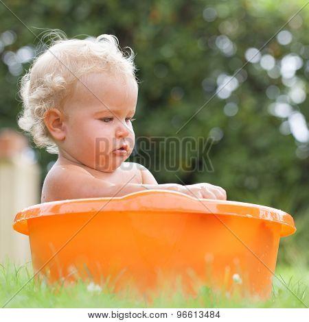 Pensive Happy Cute Curly Baby Is Bathed In Orange Pelvis
