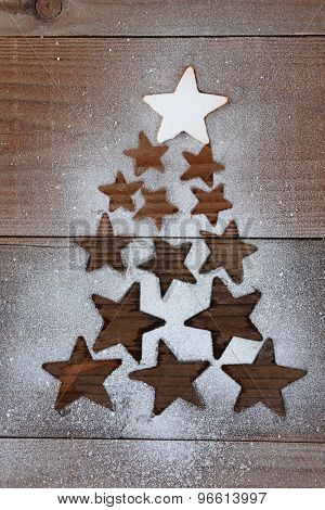 Stars forming a Christmas tree shape on a dark wood table. The top star is covered with snow while the other star shapes are void of snow. Vertical overhead view.