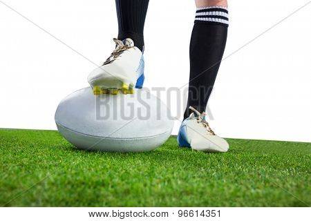 Low angle view of a rugby player posing feet on the ball