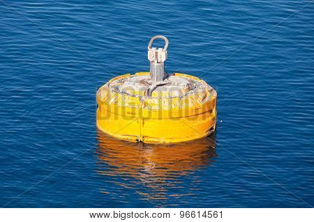 Yellow Mooring Buoy Floating On Blue Water
