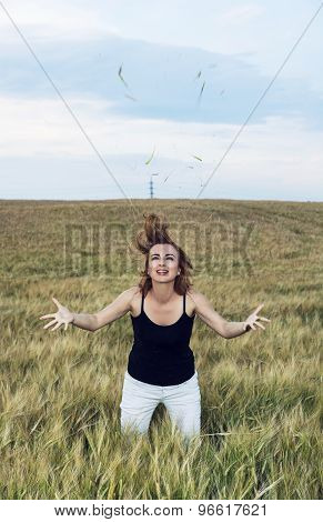 Young Woman Doing Crazy Jumps In A Wheat Field