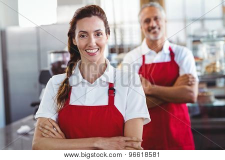 Two baristas smiling at the camera with arms crossed at the cafe