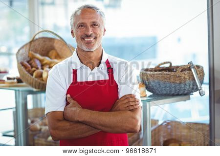 Barista smiling at camera with arms crossed in the bakery