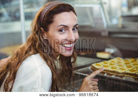 Pretty brunette pointing at pastries through the glass in the bakery store