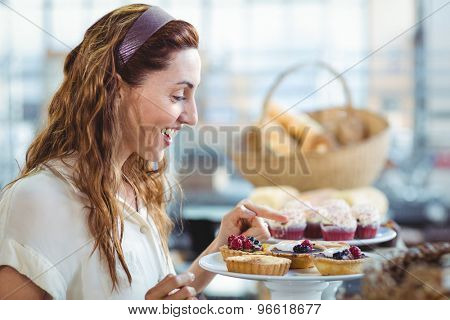 Astonished pretty woman pointing at cakes in the bakery store