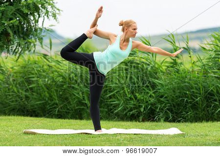 Women Make Yoga In Nature On The Green Grass,natarajasana, Lord Of The Dance Pose