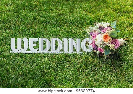 The Word Wedding With Beautifull Wedding Bouquet On A Grass