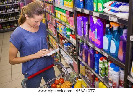 Pretty woman looking at her grocery list at supermarket