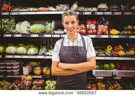 Happy pretty blonde looking at camera with arms crossed in supermarket