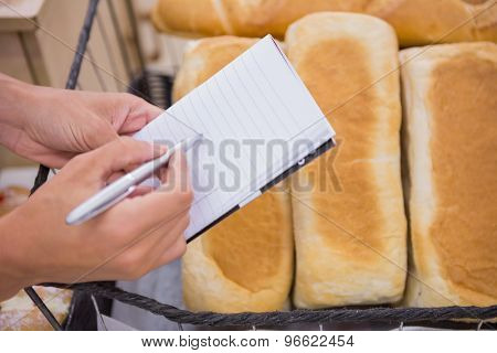 A woman writing a grocery list above bread loaf in a supermarket