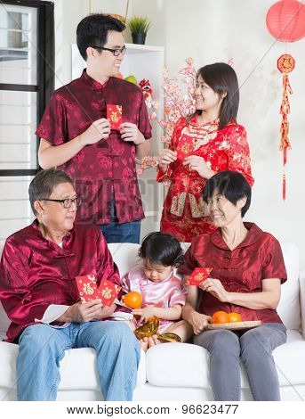 Chinese new year celebration. Happy Asian multi generations family in red cheongsam showing red packets while reunion at home.