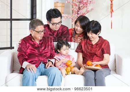 Chinese new year festival. Happy Asian multi generations family in red cheongsam reunion at home.