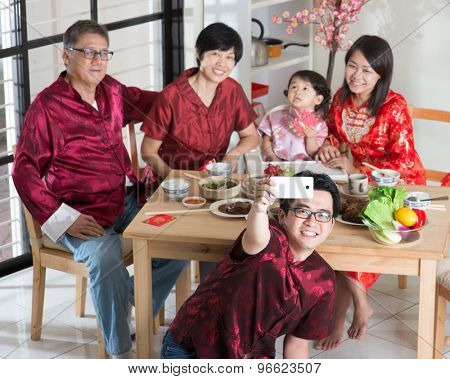 Chinese New Year, reunion dinner. Happy Asian Chinese multi generation family with red cheongsam selfie while dining at home.