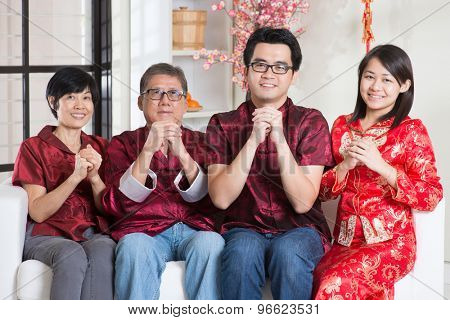 Happy Chinese new year. Happy Asian family in red cheongsam reunion and greeting at home.