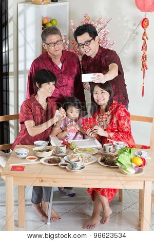 Happy Chinese New Year, taking selfie at reunion dinner. Happy Asian Chinese multi generation family with red cheongsam dining at home.