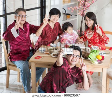 Spring seasons Chinese New Year, reunion dinner. Happy Asian Chinese multi generation family with red cheongsam selfie while dining at home.