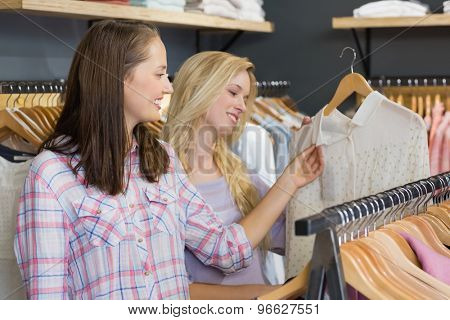 Two beautiful women touching a shirt in clothes store