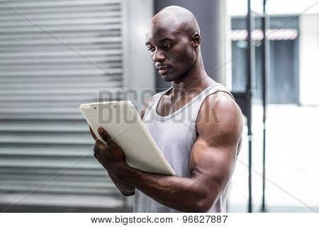 Side view of a muscular trainer writing on clipboard