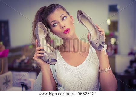 Woman holding high-heeled sandals and having fun at a shoe shop