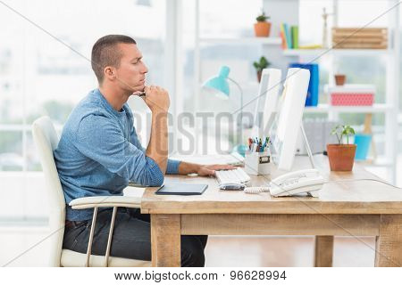 Concentrated young creative businessman working on the computer