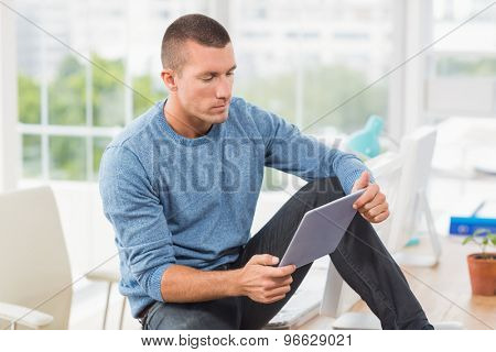 Attentive young creative businessman looking at his tablet