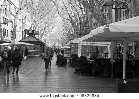 BARCELONA, SPAIN - MAR 17 2015 : Walkers stroll down La Ramblas on a rainy morning.