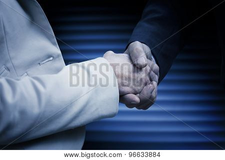 Business people shaking hands against dark grey room