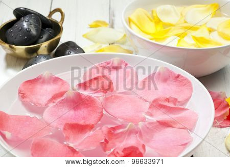 bowls with yellow and pink rose petals floating on water and massage stones