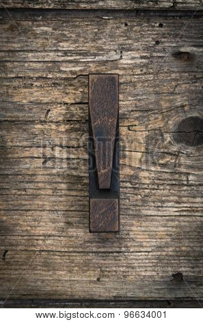 exclamation mark vintage letterpress printing block on rustic wood background