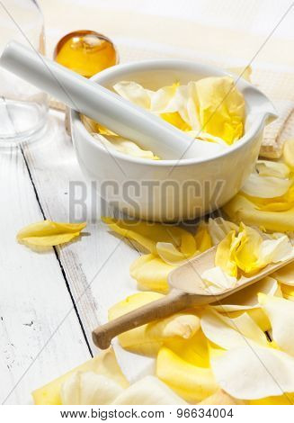 mortar and pestle with yellow rose petals on white wooden table, bottle and towel in background