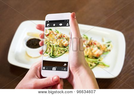 Hand holding smartphone against asian inspired fish dish with noodles and julienne vegetables