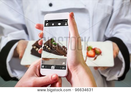 Hand holding smartphone against chef presenting chocolate cake with strawberries