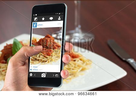 hand holding smartphone against close up of spaghetti and meatballs with red wine