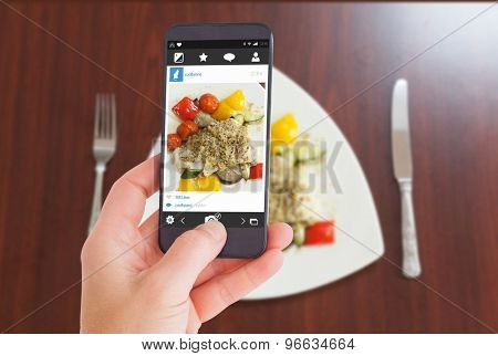 Female hand holding a smartphone against overhead view of delicious fish dish